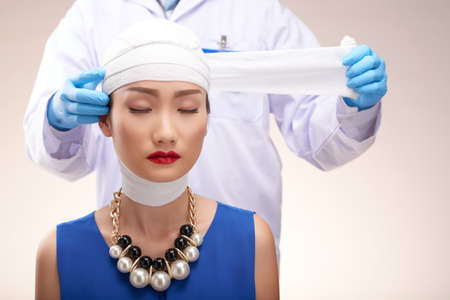 Doctor removing bandages from head of pretty Asian woman Stock Photo