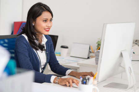 Filipina business lady busy with work on computer