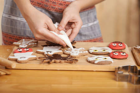 Close-up of confectioner using piping bag to decorate cookies for Halloween