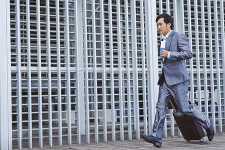 puntualidad: Empresario vietnamita con maleta corriendo tarde para el vuelo