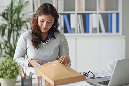 correspondence: Señora de negocios que llena el sobre con documentos de negocios