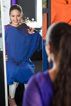 Beautiful smiling woman trying on dress in front of mirror Stock Photo