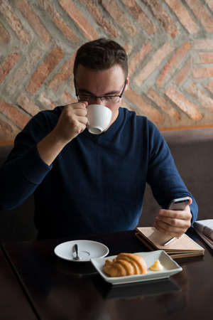 wireless telephone: Businessman enjoying morning coffee and reading text message on his smartphone Stock Photo
