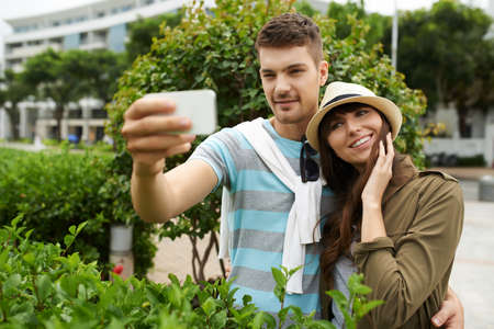 couples hug: Handsome young man taking selfie with his beautiful girlfriend