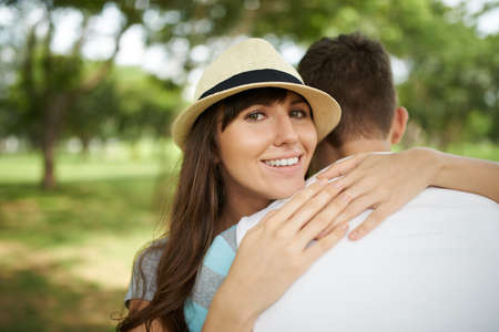couples hug: Portrait of happy woman embracing her boyfriend and looking at the camera