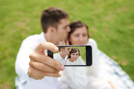 couples hug: Young man taking selfie of him kissing his girlfriend, focus on smartphone screen Stock Photo