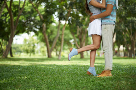 Cropped image of couple kissing in the park: love and relationship concept