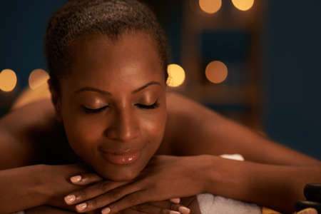 Face of beautiful African-American woman with perfect skin having spa treatment