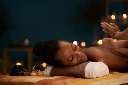 African-American woman receiving professional back massage in spa salon