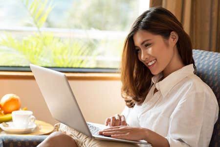 comfortable: Young Vietnamese woman sitting in comfortable armchair and working on laptop at home