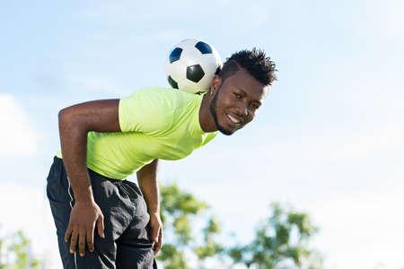 Smiling soccer player balancing ball on his neck