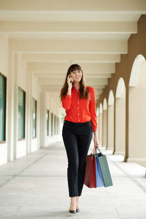Pretty beautiful woman with shopping bags walking and talking on the phone Stock Photo
