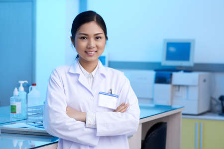Portrait of beautiful young female chemist in modern laboratory