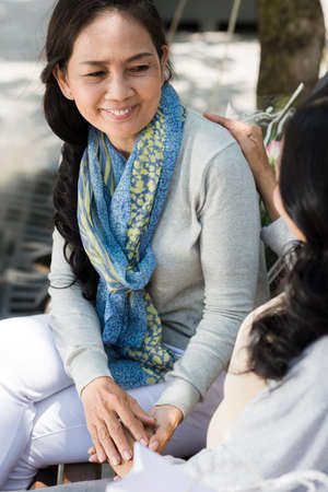 Smiling Vietnamese woman talking to her best friend Stock Photo