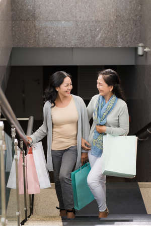 upstairs: Cheerful women with shopping bags going upstairs Stock Photo