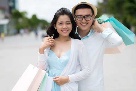 Hugging Asian couple with paper bags standing smiling and looking at the camera