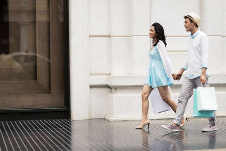 Young Asian couple on a city street after shopping
