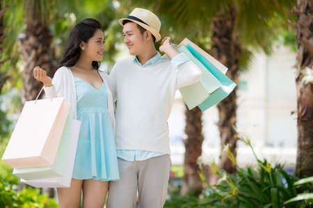 Young man with shopping bags looking at his beautiful girlfriend Stock Photo