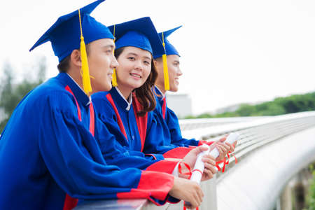 Smiling Asian graduating students with their diplomas standing outdoors Reklamní fotografie