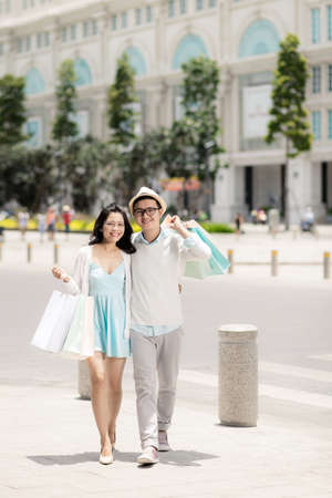 Full-length portrait of cheerful Vietnamese couple with many shopping bags Stock Photo