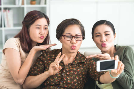 Family making duck face while taking a selfie Stock Photo
