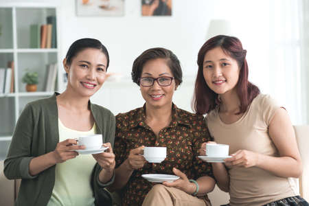 three generations of women: Female generations of Vietnamese family drinking tea and looking at the camera