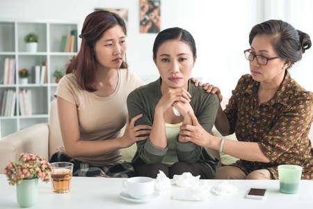 persona deprimida: Daughter and mother reassuring sad depressed woman