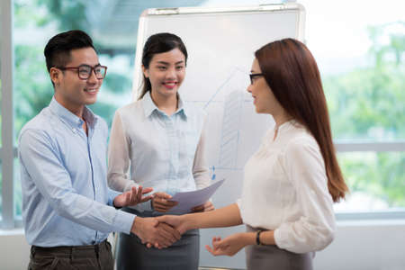 Young vietnamese businessman greeting his female colleague stock stock photo young vietnamese businessman greeting his female colleague m4hsunfo