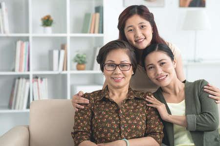 Adolescente asiatique embrassant sa mère et sa grand-mère Banque d'images