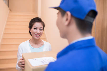 post man: Asian woman is happy to receive a parcel Stock Photo