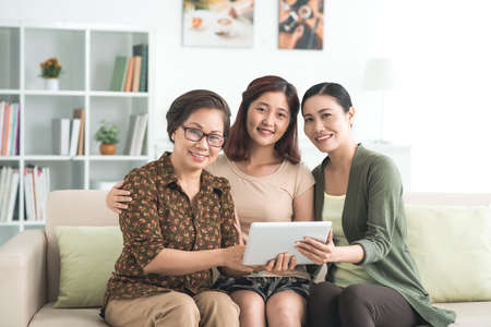 three generations of women: Smiling Vietnamese family of three using digital tablet at home