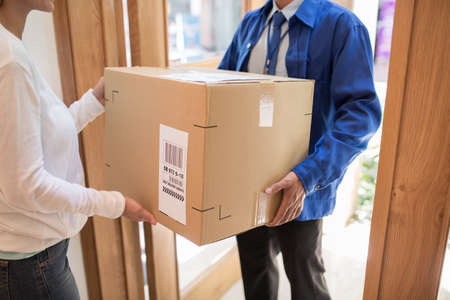 Delivery man bringing big package to the customers door