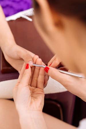 Manicurist using steel cuticle pusher during procedure Stock Photo