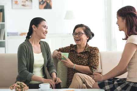 Grandmother, mother and daughter drinking tea and having good time together Фото со стока