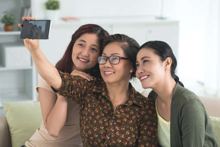 Mulher sênior que toma o selfie com suas duas filhas Foto de archivo - 73545189