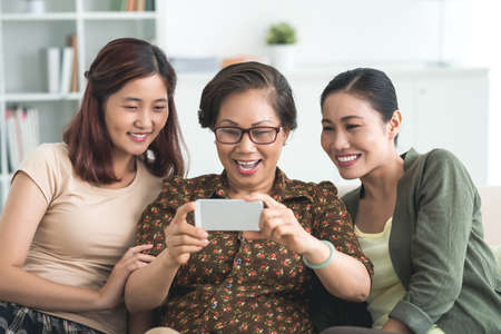 three generations of women: Senior woman, her daughter and granddaughter watching funny video on the smartphone