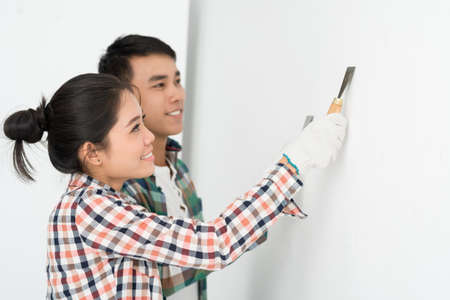 putty knives: Young couple aligning a wall in their hew house Stock Photo