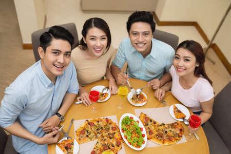 Happy Vietnamese friends enjoying tasty pizza, selective focus Stock Photo