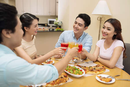 happy asian people: Four young people talking and drinking cocktails at the dinner Stock Photo