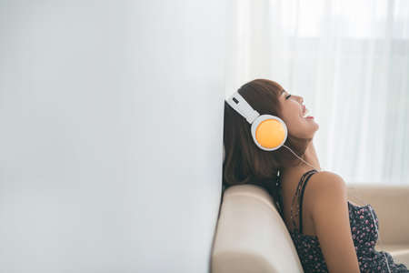 Laughing young woman in headphones listening to the radio Stock Photo