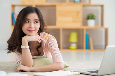 Dreamy schoolgirl with a laptop lying on the floor Stock Photo