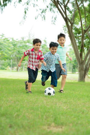 Little boys playing soccer in the park