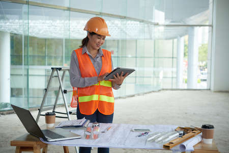 female construction worker: Smiling female construction worker reading something on tablet computer Stock Photo