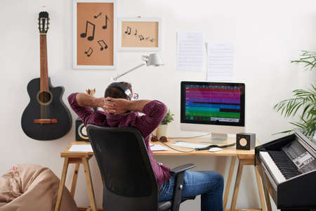 Sound designer sitting in chair and listening to new music track on his computer Stock Photo