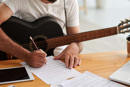 Close-up image of man writing music for new album