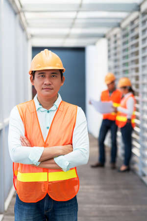 Portrait of Vietnamese civil engineer wearing hardhat and vest