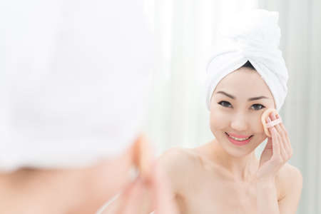 Attractive Asian woman using puff to apply powder Stock Photo