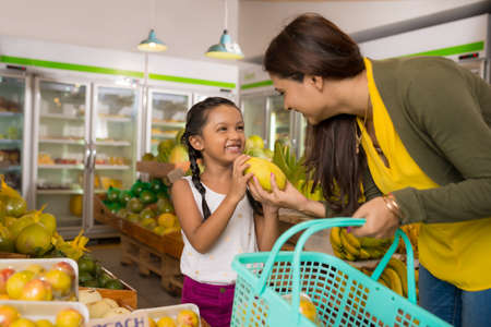 Indian mother and daughter choosing fruits at the grocery store