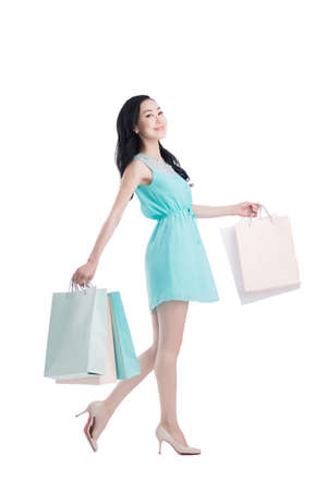 or spree: Happy young woman walking with shopping bags