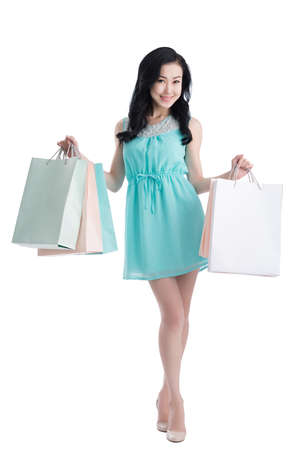 Attractive Asian girl with paper bags smiling and looking at the camera